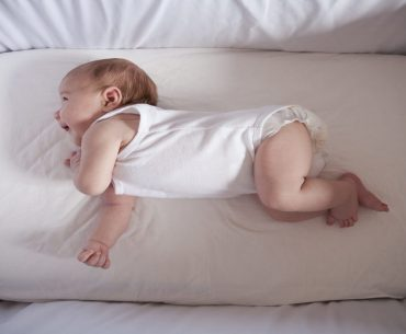 newborn-laughing-on-crib sheet