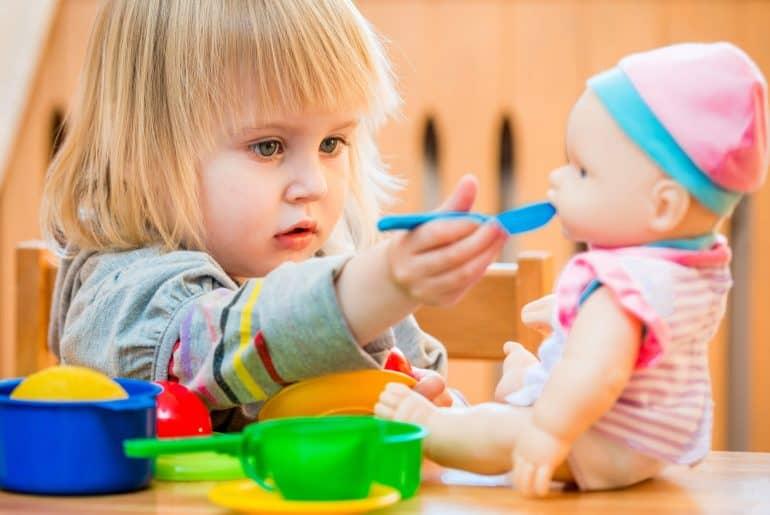 Girl feeding a smart doll